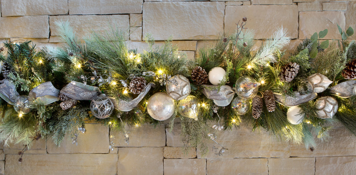 Elegant textured white, silver, and clear ornaments, with snow-frosted pinecones. Silver accents and ribbon pulling the whole piece together.