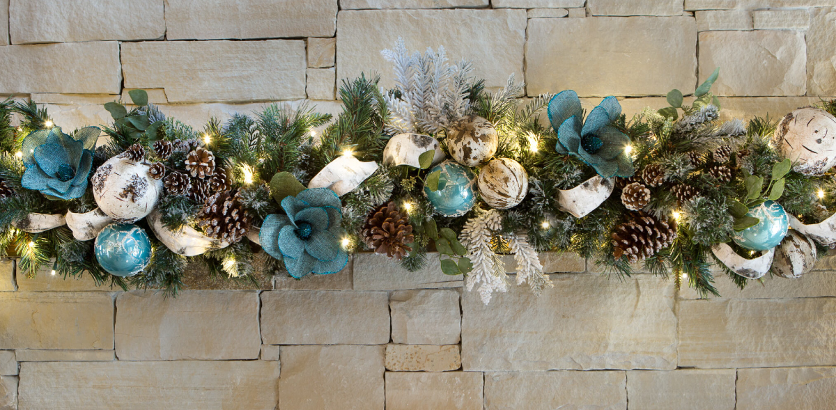 Cozy snow flocked picks, teal and birch ornaments. Frosted pinecones and teal burlap magnolias for accents.
